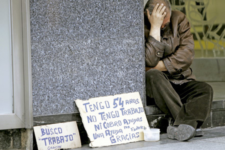 hombre sin techo en la calle con carteles de Busco trabajo