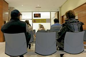 personas paradas en la sala de espera de una oficina de empleo