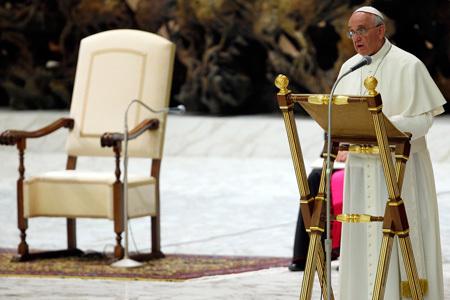 papa Francisco habla de pie en el micrófono durante una audiencia