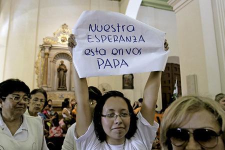 mujer sostiene un cartel Nuestra esperanza está en vos, Papa