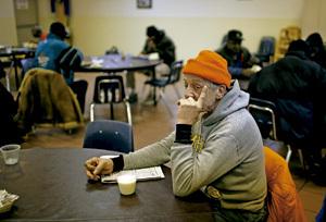 hombre sin techo mendigo en un comedor social de Cáritas