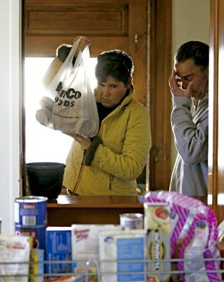 mujer recoge una bolsa de comida en un centro de Cáritas