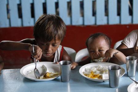 dos niños comiendo en un país empobrecido