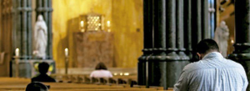 padre e hijo rezando en los bancos de una iglesia vacía