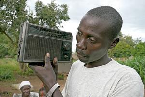 Hombre escucha un transistor de Radio Wa, Uganda
