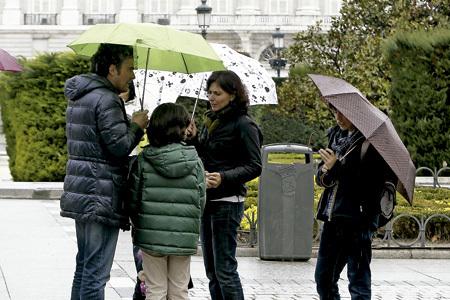 familia en la calle con paraguas en un día de lluvia