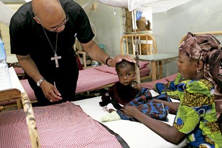 obispo africano consuela a un niño enfermo de sida en un hospital católico en África