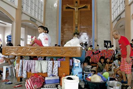 fieles católicos en Filipinas se refugian en una iglesia tras el paso del tifón Haiyan noviembre 2013