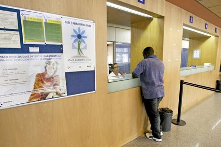 inmigrante ante un mostrador de un hospital de la Seguridad Social