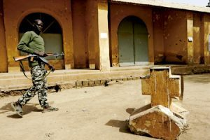 soldado de Malí junto a una tumba cristiana