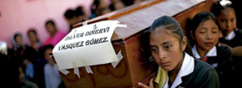 varias chicas jóvenes portan un ataúd en Guatemala