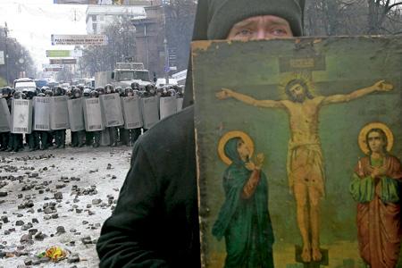 sacerdote cristiano mediando entre la policía y los manifestantes en Ucrania