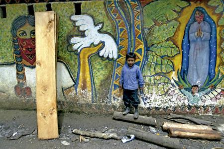 niño frente a un mural zapatista en Chiapas