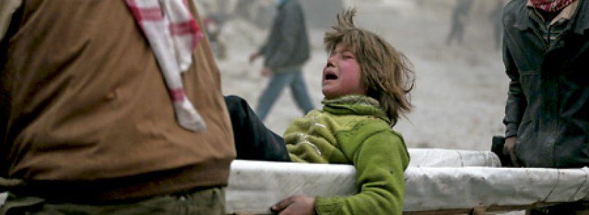 niño trasladado en camilla después de ser herido en Siria