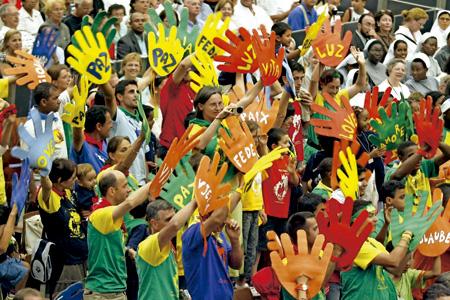 peregrinos en una audiencia general con el papa Francisco agitan manos gigantes de colores con mensajes de paz y amor