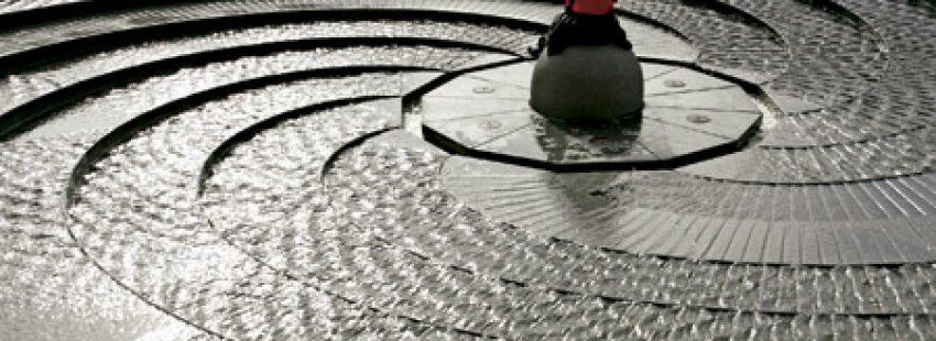 hombre sentado en medio de una fuente circular de piedra