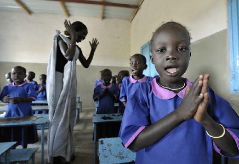 niñas pequeñas rezando alumnas en una escuela católica de África