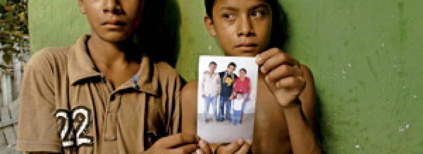 dos niños enseñan la foto de sus padres asesinados en Guatemala