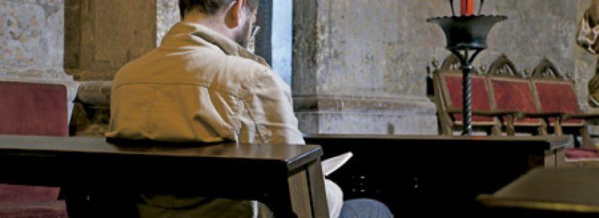 hombre en una iglesia rezando en soledad