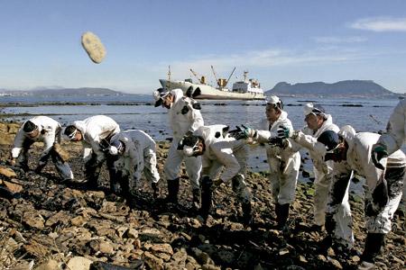 hombres limpian petróleo en una playa