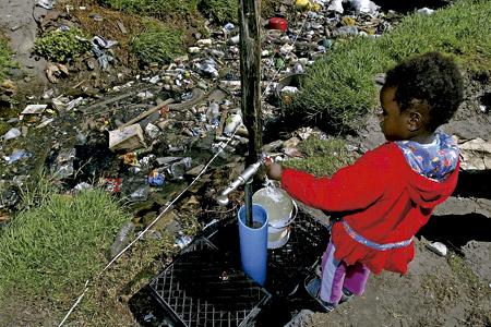 niña en África coge agua en dos bidones
