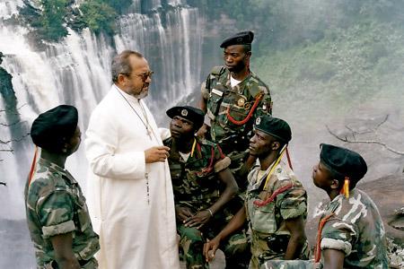 sacerdote habla con militares africanos en una zona en conflicto