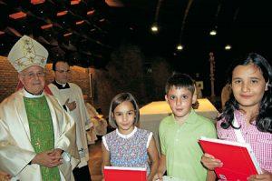 Blázquez entrega el nuevo catecismo a los niños.