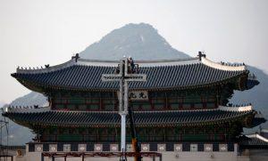 Operarios surcoreanos instalan un cruz por la visita del Papa.