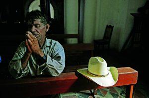 Salvadoran prays during Mass in El Salvador