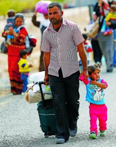 Syrian Kurdish refugees walk with their belongings after crossing into Turkey