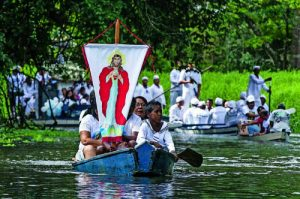 Pilgrims display banner with image of Christ during 2012 river procession in Brazil