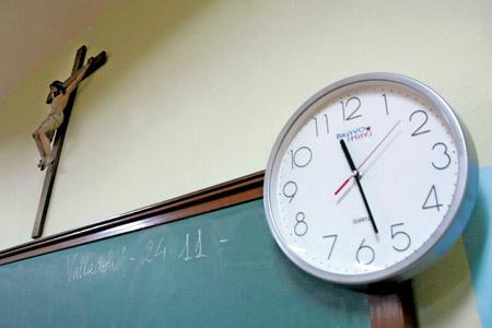 aula católica con crucifijo y reloj encima de la pizarra