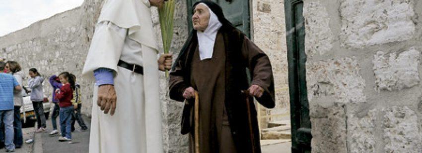 un religioso habla con una monja con hábito