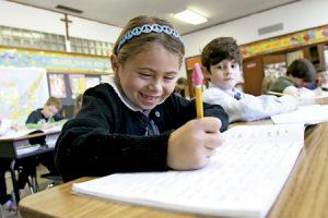 niña pequeña alumna en la escuela haciendo deberes