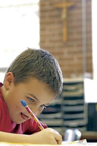 niño pequeño alumno en la escuela escribiendo