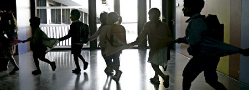 niños pequeños alumnos en la escuela en un pasillo a contraluz