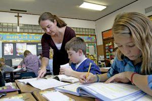 profesora con niños pequeños haciendo los deberes en un colegio católico