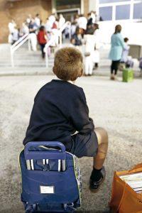 niño en el patio del colegio solo esperando que vengan a recogerlo