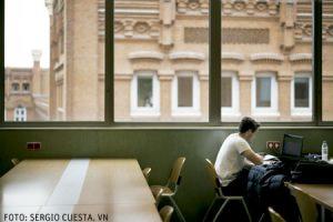 alumno chico joven en la universidad biblioteca estudiando con el ordenador