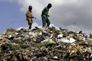 niños caminan sobre una montaña de basura contaminación