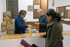 economato de Cáritas voluntarios repartiendo comida a solicitantes