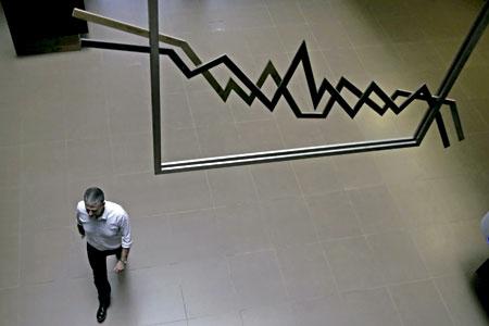 un hombre camina en la Bolsa debajo de un gráfico de resultados económicos