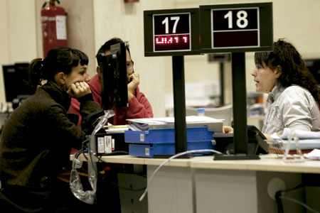 personas paradas buscan trabajo en una oficina de empleo