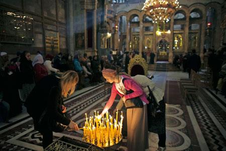 cristianos encienden velas y rezan en el Santo Sepulcro de Jerusalén