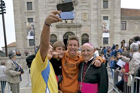 dos jóvenes se hacen un selfie con el obispo de Ávila, Jesús García Burillo