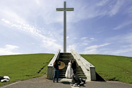 novios haciendo reportaje fotográfico de boda delante de una cruz