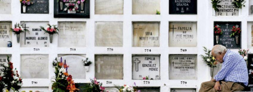 hombre mayor en un cementerio reza pensativo delante de las lápidas