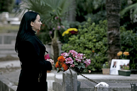 madre en el cementerio delante de una tumba