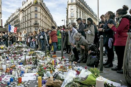 gente rezando en uno de los escenarios de los atentados de París 13 noviembre 2015
