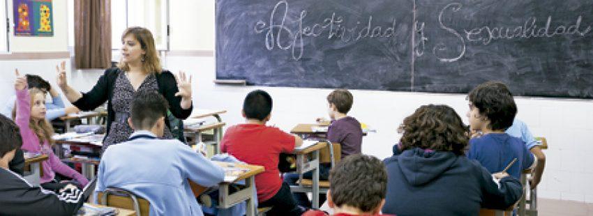 alumnos en la escuela católica con profesora que está explicando educación sexual con valores cristianos
